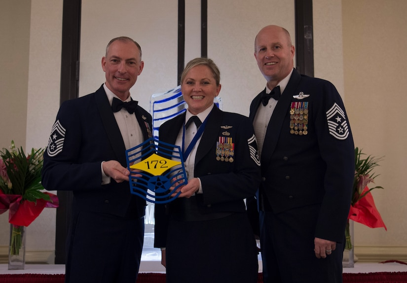 Chief Master Sgt. Larry C. Williams, U.S. Air Force Expeditionary Center command chief, left, recognizes Senior Master Stephanie Northup, 43rd Operations Support Squadron superintendent, center, along with Chief Master Sgt. Todd Cole, 628th Air Base Wing command chief, right, during the chief master sergeant recognition ceremony at the Charleston Club Feb. 10, 2018.