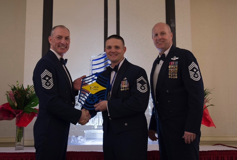 Chief Master Sgt. Larry C. Williams, U.S. Air Force Expeditionary Center command chief, left, recognizes Senior Master Sgt. Michael Stone, 437th Aircraft Maintenance Squadron superintendent, center, along with Chief Master Sgt. Todd Cole, 628th Air Base Wing command chief, right, during the chief master sergeant recognition ceremony at the Charleston Club Feb. 10, 2018.