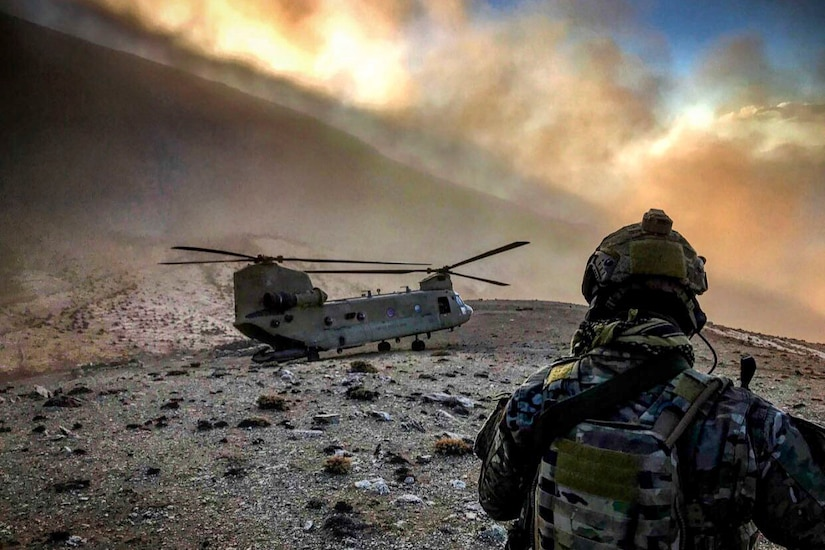 An airman, shown from behind, looks at a helicopter grounded on sparse, rocky terrain as clouds waft above.