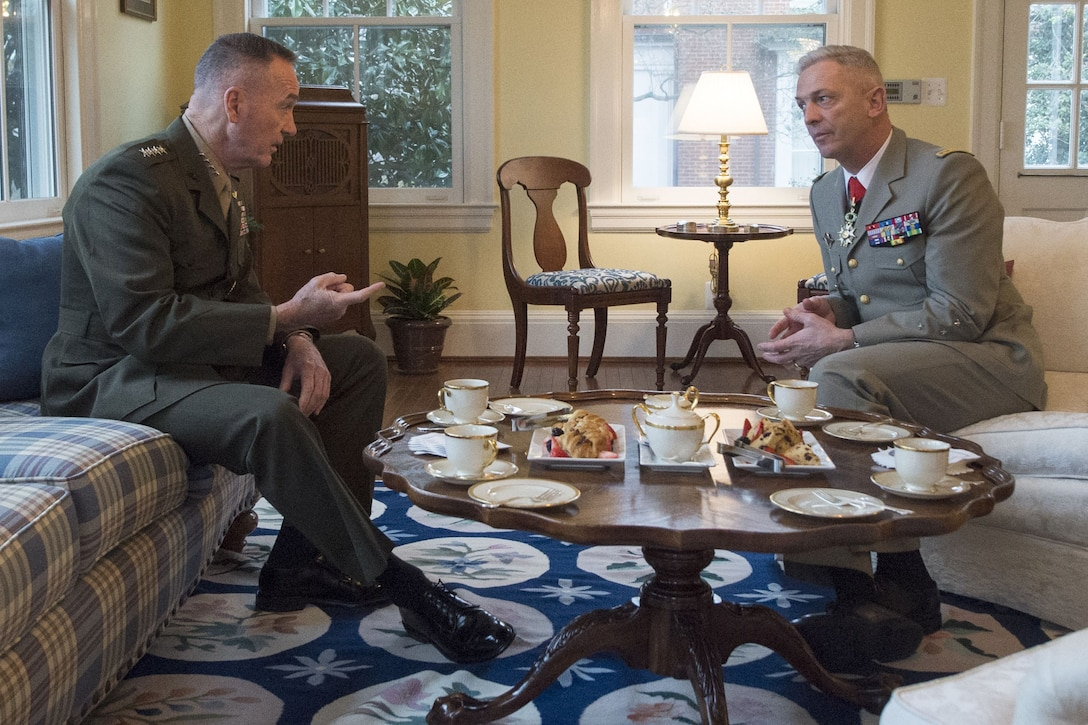 Marine Corps Gen. Joe Dunford sits on a couch and talks with his French counterpart, sitting across from him.