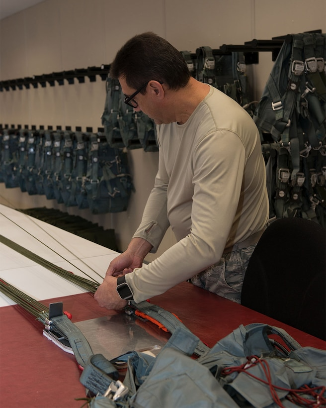 Master Sgt. Raymond Rosado counts parachute lines to ensure the lines are not tangled or frayed 1 Feb 2018 at Bradley Aire National Guard Base, East Granby, Conn. One of Rosado's duties include inspecting survival equipment, like parachutes, for any deficiencies. (U.S. Air National Guard photo by 1st Lt. Jen Pierce/released)