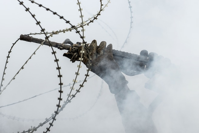 Hands holding a rifle hold up strings of barbed wire against a smoky backdrop.