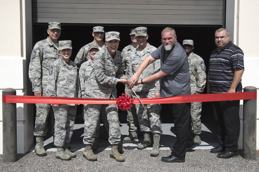 U.S. Air Force Col. April Vogel, commander of the 6th Air Mobility, and James Norbech, the medical program director with the 6th Medical Group, participate in a ribbon cutting ceremony at MacDill Air Force Base, Fla., Feb. 9, 2018.
