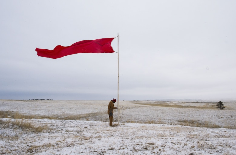 Staff Sgt. Nathan Rust, 90th Security Support Squadron combat arms instructor, raises the range flag