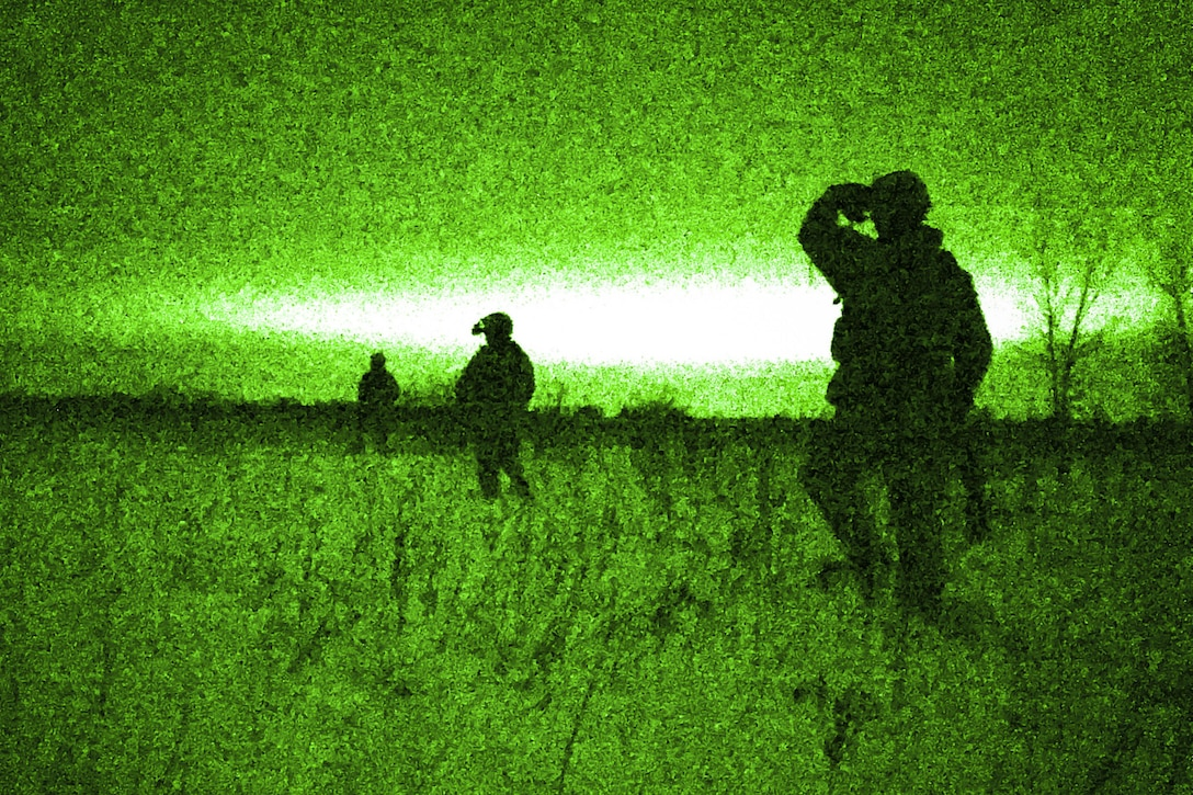 Airmen, shown in silhouette, walk in a field, illuminated in green from a night vision lens.