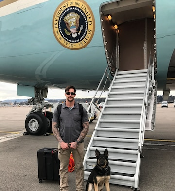 Air Force Staff Sgt. Michael Hensley, 52nd Security Forces Squadron military working dog handler, and Tina, 52nd SFS MWD, stand outside Air Force One Jan. 26, 2018. Two MWD teams were part of the security detail for President Donald J. Trump's visit to Davos, Switzerland for the World Economic Forum, where they worked alongside Secret Service dog teams.