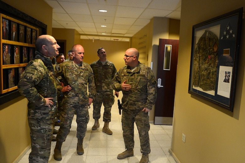 Gen. Mike Holmes, commander of Air Combat Command, and Chief Master Sgt. Frank Batten, ACC command chief, receives a Heritage Room brief from Tech. Sgt. Jose Valdez, 455th Air Expeditionary Wing command and control controller, Feb. 9, 2018 at Bagram Airfield, Afghanistan.