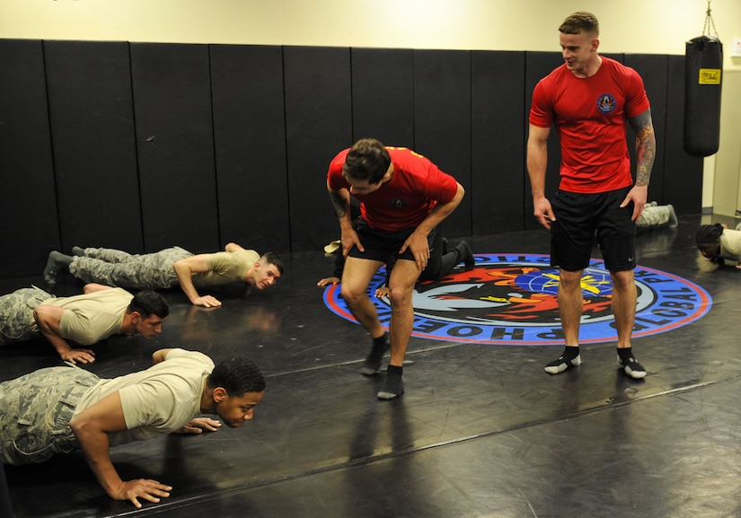 Staff Sgt. George Carty, center, 628th Security Forces Squadron Phoenix Raven and Senior Airman Cody Linday, right, 628th SFS Phoenix Raven, motivate candidates during the push-up portion of a physical training exercise Jan. 31, 2018, at Joint Base Charleston, S.C.