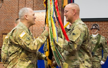 (Left) Maj. Gen. Bruce Hackett, commander of the 80th Training Command, receives the unit's guidon from Command Sgt. Maj. Jeffrey Darlington at the command's change of responsibility ceremony held at the Defense Supply Center Richmond, Virginia, during the 80th TC Commander's Readiness Workshop Feb. 8, 2018.  As the outgoing senior enlisted leader of the 80th TC, Darlington handed over the reins to the incoming senior enlisted leader Command Sgt. Maj. Dennis Thomas. (U.S. Army Reserve Photo by Maj. Addie Leonhardt)