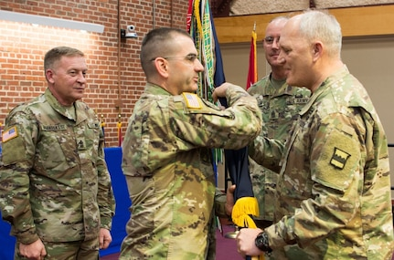 (Right) Maj. Gen. Bruce Hackett, commander of the 80th Training Command, passes the unit's guidon to Command Sgt. Maj. Dennis Thomas at the 80th's change of responsibility ceremony held at the Defense Supply Center Richmond, Virginia, during the 80th TC Commander's Readiness Workshop Feb. 8, 2018.  Sgt. Maj. Gerald Brandsasse (far left) looks on. (U.S. Army Reserve Photo by Maj. Addie Leonhardt)