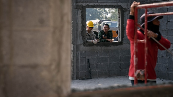 "U.S. Army Spc. Bernard Fausto watches construction alongside his Royal Thai Army friend named ""Dome"" during construction of a school building at Nongphipadungkitwittaya School in Korat, Kingdom of Thailand, Feb. 7, 2018. Fausto is a horizontal engineer with 797th Engineering Company, 411th Engineer Battalion, and is a native of Tamuning, Guam. Humanitarian civic assistance projects conducted during the exercise support the needs and humanitarian interests of the Thai people. Cobra Gold 18 is an annual exercise conducted in the Kingdom of Thailand held from Feb. 13-23 with seven full participating nations."