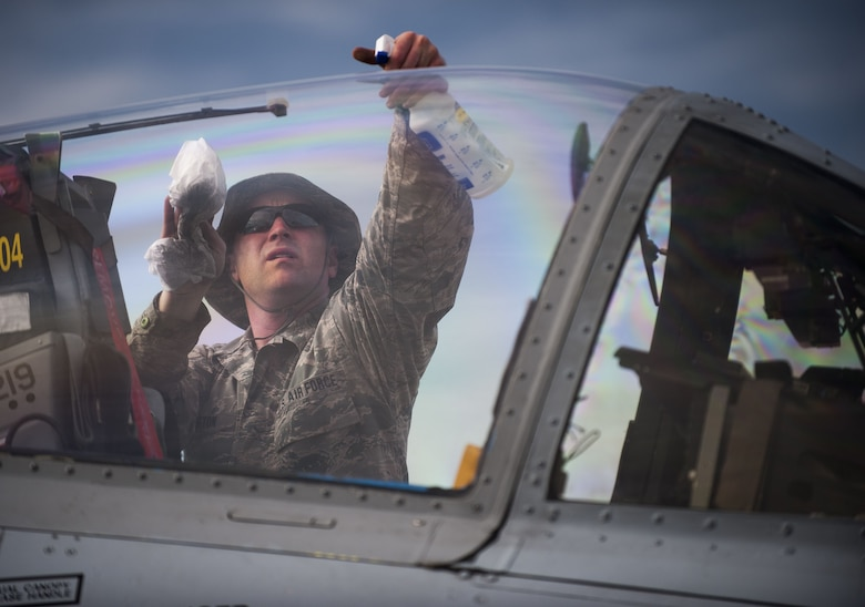 """Staff Sgt. Aaron Barton, a crew chief with the 122nd Fighter Wing, cleans conducts a preflight inspection on an A-10C Thunderbolt II """"Warthog"""" aircraft during Operation Guardian Blitz, Jan 25, 2018, at MacDill Air Force Base, Fla. Guardian Blitz is a two-week joint exercise to improve service interoperability for combat search and rescue and close air support. (U.S. Air National Guard photo by Staff Sgt. William Hopper/Released)"""