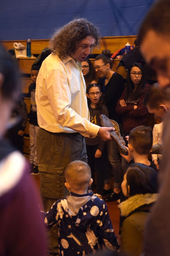 Eddy Collier, shows children a dinosaur fossil before starting the digital dome science show at RAF Mildenhall, England, Feb. 10, 2018. Families could also take Valentine's Day themed family photos and enjoy various family activities together such as, storytime and arts and crafts before and after the shows. (U.S. Air Force photo by Airman 1st Class Alexandria Lee)