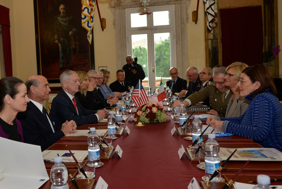 Defense Secretary James N. Mattis sits at a long table with other officials across from his Italian counterpart.