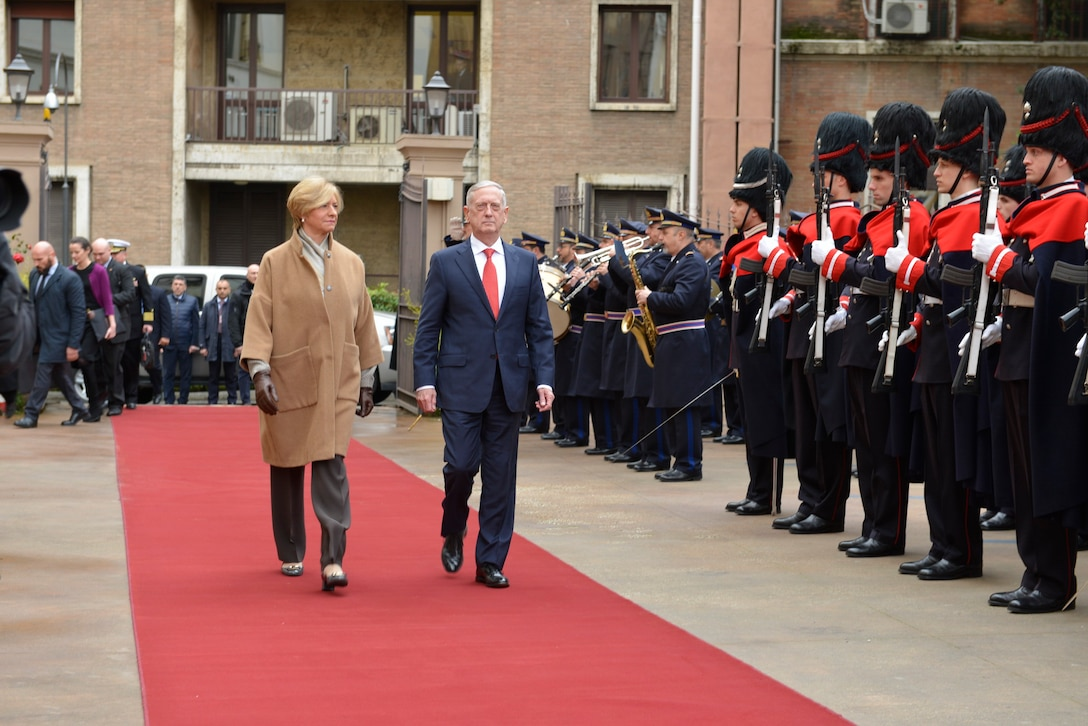 Defense Secretary James N. Mattis walks with Italian Defense Minister Roberta Pinotti on a red carpet past an honor guard.