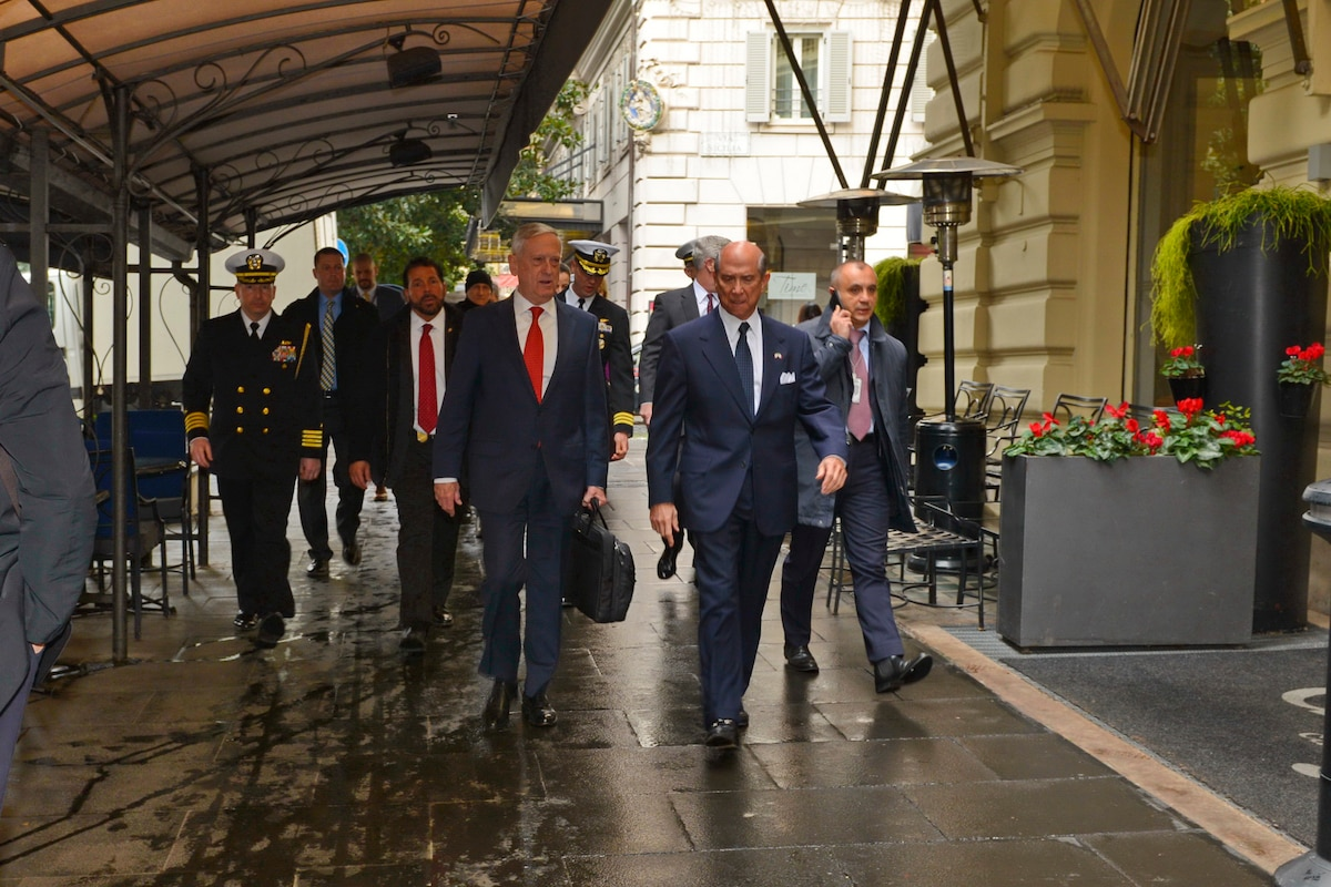 Defense Secretary James N. Mattis walks with the U.S. ambassador under an awning in Rome.