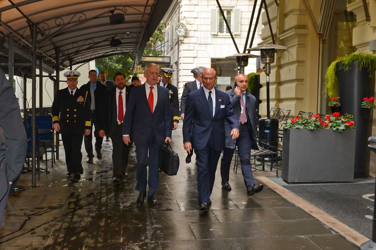 Defense Secretary James N. Mattis walks with the U.S. ambassador under an awning in Rome.
