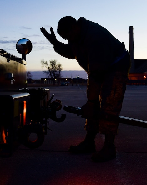 Master Sgt. Jeremie Washington, the 28th Maintenance Squadron production superintendent of aerospace ground equipment, guides a driver at Ellsworth Air Force Base, S.D., Feb. 2, 2018. Cargo returning from deployments is unloaded by the 28th Logistics Readiness Squadron and returned to its respective units. (U.S. Air Force photo by Senior Airman Randahl J. Jenson)