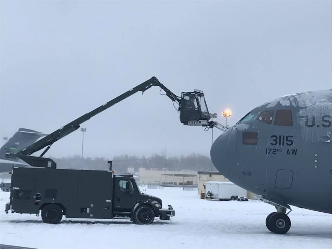 Airmen assigned to the 821st Contingency Response Group de-ice a C-17 Globemaster cargo aircraft during the Rapid Alaskan Airlift Week exercise at Eielson Air Force Base, Alaska.