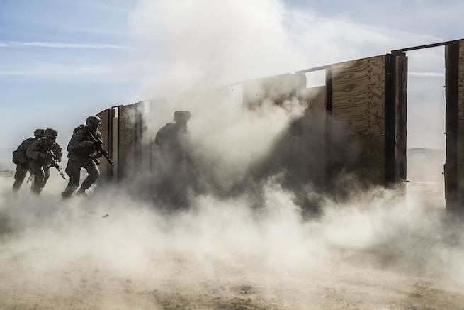 Marines participate in training to breach doors as smoke rises.