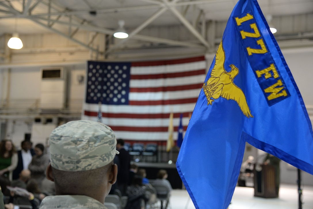 A picture of a member of the New Jersey Air National Guard's 177th Fighter Wing standing with the wing's guidon.