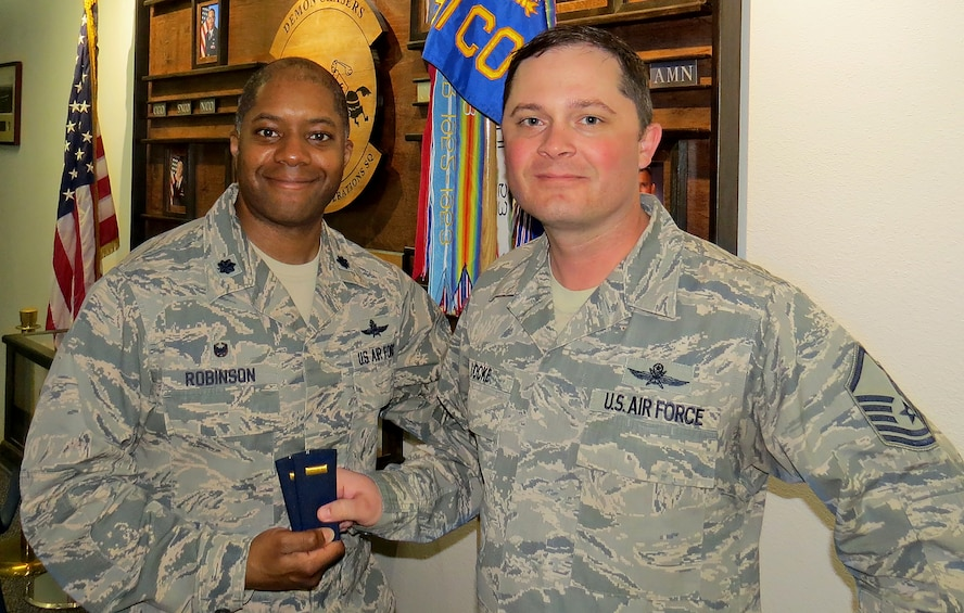 Lt. Col. Christopher Robinson, 91st Cyberspace Operations Squadron commander, hands second lieutenant ranks to Master Sgt. Micheal Locke, 91st COS operations superintendent, to celebrate his selection as a candidate for the newly authorized cyber direct appointment program. Upon successful completion of the program, Locke will commission as a second lieutenant. (Courtesy photo)