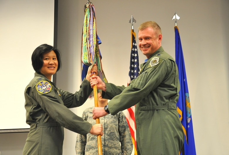 Col. Janette Thode, 340th Flying Training Group commander, accepts the guidon from Lt. Col. Allen Duckworth, outgoing 97th Flying Training Squadron commander. (U.S. Air Force photo by Debi Smith)