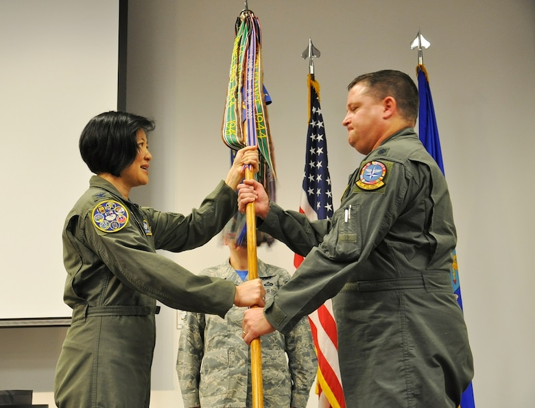 New 97th Flying Training Squadron Commander Lt. Col. Michael Rose accepts the guidon, and command of the squadron, from 340th Flying Training Group Commander Col. Janette Thode. (U.S. Air Force photo by Debi Smith)