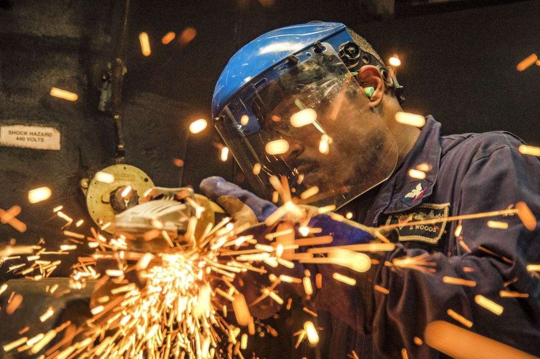 A sailor grinds a piece of metal in a ship's machine shop.