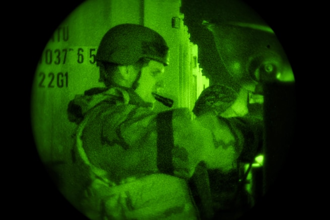An airman holds a flashlight in his mouth during an exercise under a green light.