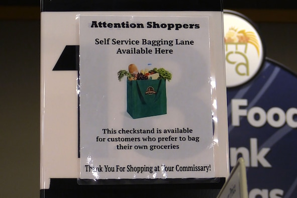 PETERSON AIR FORCE BASE, Colo. - A sign designating the Self Service Bagging Lane hangs at check stand 18 at the Peterson Air Force Base, Colorado Commissary. Customers can look for an identical sign at check stand one on the opposite side of the store. Self-service bagging at the two check stands is part of a customer service test conducted by the Defense Commissary Agency Jan. 25, 2018. (U.S. Air Force photo by Tech. Sgt. Joshua Arends)