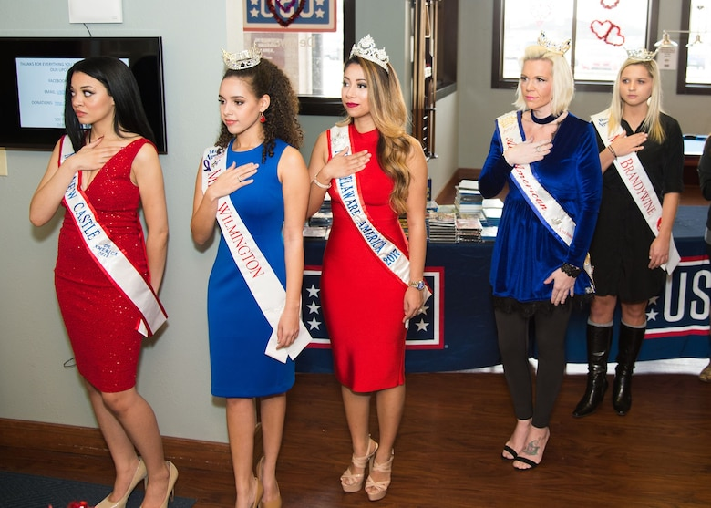 Delaware beauty queens pay respect to the flag during the singing of the National Anthem at the National Pizza Day event Feb. 9, 2018, at the USO on Dover Air Force Base, Del.  The anthem was sung by Rebecca Gasperetti, Miss Hockessin 2018, Miss America System. (U.S. Air Force photo by Mauricio Campino)
