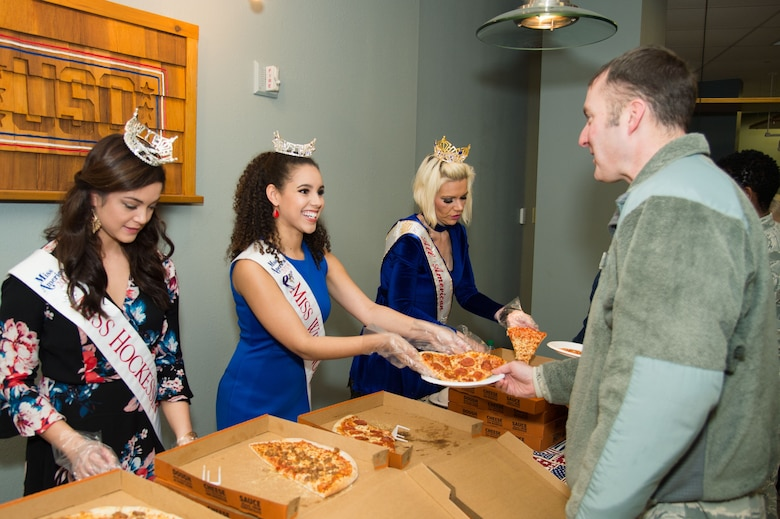 Rebecca Gasperetti, Miss Hockessin 2018, Miss America System; Joanna Wicks, Miss Wilmington 2018, Miss America System; and Allison Rae Funds, All American Ambassador 2018, serve lunch to Team Dover Airmen and their families at the National Pizza Day event Feb. 9, 2018, at the USO on Dover Air Force Base, Del. Over 80 Airmen and their families enjoyed free lunch donated by the USO. (U.S. Air Force photo by Mauricio Campino)