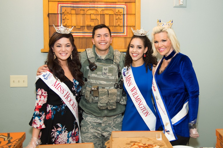 Staff Sgt. Andrew Lowe, 436th Security Forces Squadron response force leader, poses for a photo with Rebecca Gasperetti, Miss Hockessin 2018, Miss America System; Joanna Wicks, Miss Wilmington 2018, Miss America System; and Allison Rae Funds, All American Ambassador 2018, during the National Pizza Day event Feb. 9, 2018, at the USO on Dover Air Force Base, Del.  After serving lunch at the USO, the beauty queens delivered pizzas to the 436th Civil Engineer Squadron fire station. (U.S. Air Force photo by Mauricio Campino)