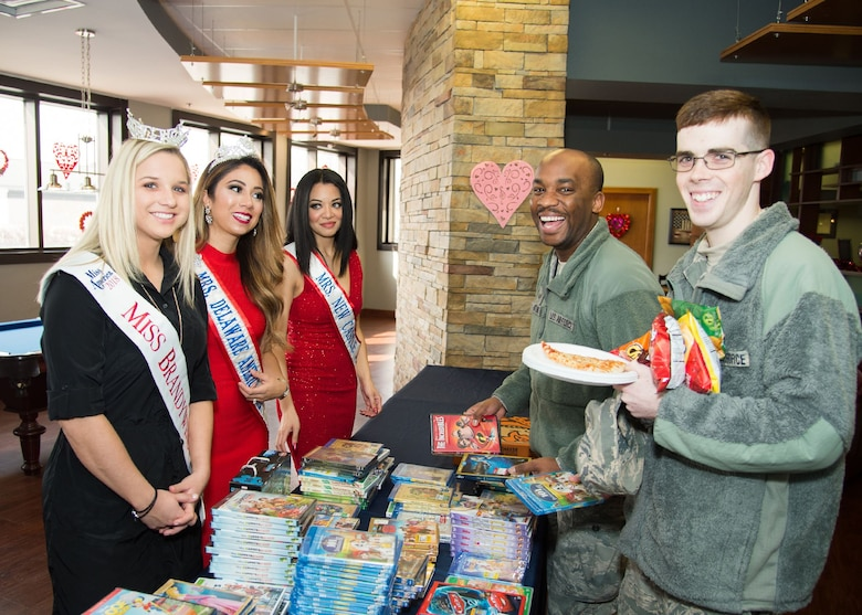 Jordan Jones, Miss Brandywine 2018, Miss America System; Angel Paro-Pringle, Mrs. New Castle, Delaware America 2018; and Ivana Hamilton, Mrs. Delaware America 2017, hand out free DVD movies to members of Team Dover at the National Pizza Day event Feb. 9, 2018, at the USO on Dover Air Force Base, Del.  The USO gave out over 150 free DVD movies to Airmen and their families. (U.S. Air Force photo by Mauricio Campino)