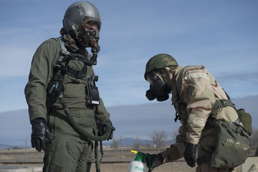 Image of A 366th Operations Support Squadron Airman simulates decontaminating a 366th Fighter Wing pilot Feb. 7, 2018, at Mountain Home Air Force Base, Idaho. The base participated in a week-long exercise to train for potential real-world contingencies. (U.S. Air Force photo by Airman 1st Class JaNae Capuno)