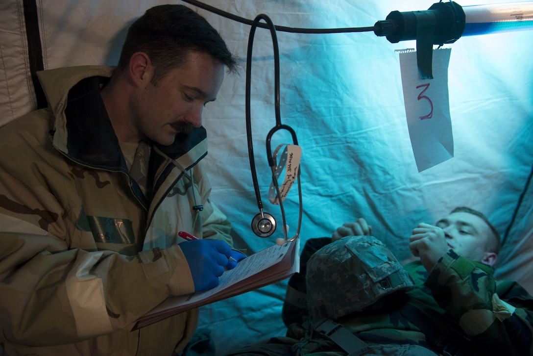 Image of Staff Sgt. Daniel Cobb, a 366th Medical Group paramedic, assesses Airman 1st Class Justin Kuhn, 366th Logistics Readiness Squadron central storage apprentice, for a simulated broken leg Feb. 7, 2018, at Mountain Home Air Force Base, Idaho. The base participated in a week-long exercise to train for potential real-world contingencies. (U.S. Air Force photo by Airman 1st Class JaNae Capuno)