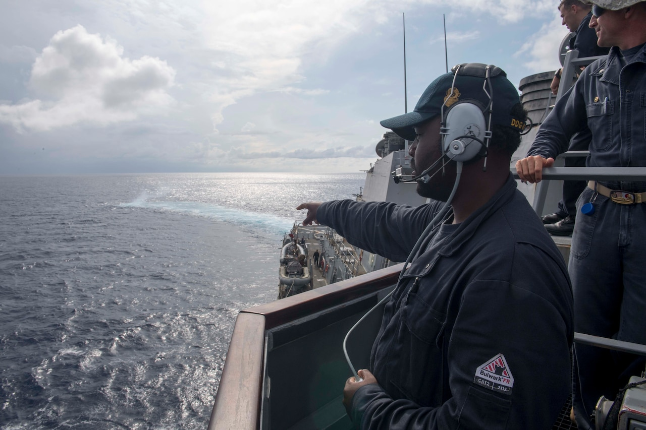 Navy Seaman Dorsey Cadette assigned to the guided-missile destroyer USS Stethem, points out a smoke signal during man-overboard training while conducting routine operations in the South China Sea.