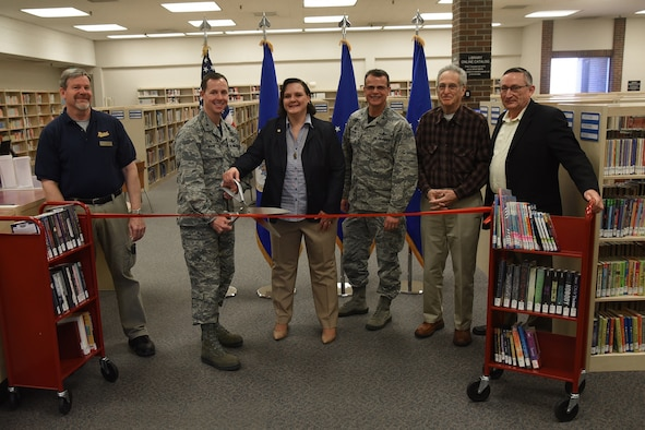 Col. Todd Moore (Left), 21st Space Wing commander and Rebecca Perkins (Right), 21st Force Support Squadron supervisory librarian perform a ribbon cutting ceremony at the library on Peterson Air Force Base, Colorado, Feb. 9, 2018. The library was refurbished with new paint, texture, and furniture.
