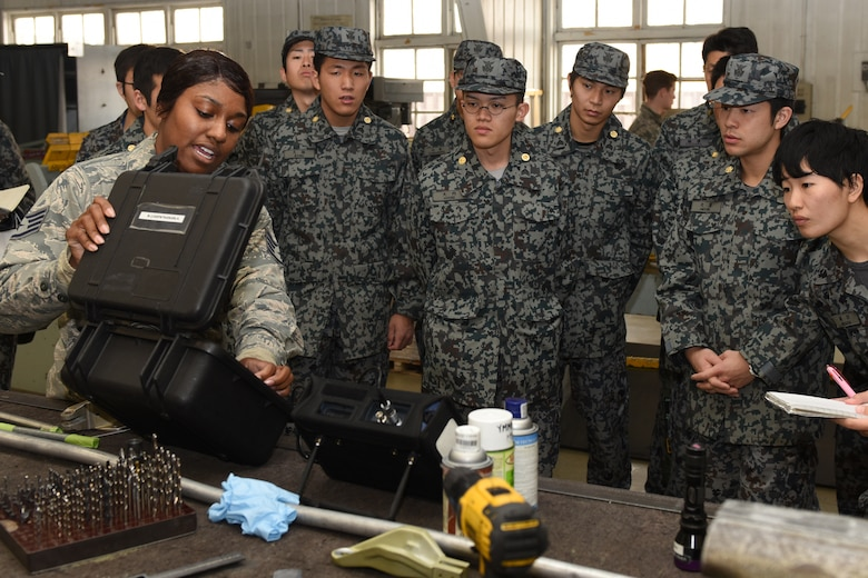 U.S. Air Force Staff Sgt. Kayla Hayes, 374th Maintenance Squadron non-destructive inspection journeyman, showcases an Eddy-current testing kit to visiting Koku Jietai Cadets during a Basic Maintenance Officer Tour at Yokota Air Base, Japan, Feb. 1, 2018.