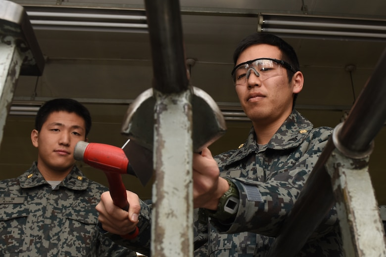 A Koku Jietai Cadet bends sheet metal as part of his visit to the 374th Maintenance Squadron fabrication flight during a Basic Maintenance Officer Tour at Yokota Air Base, Japan, Feb. 1, 2018.