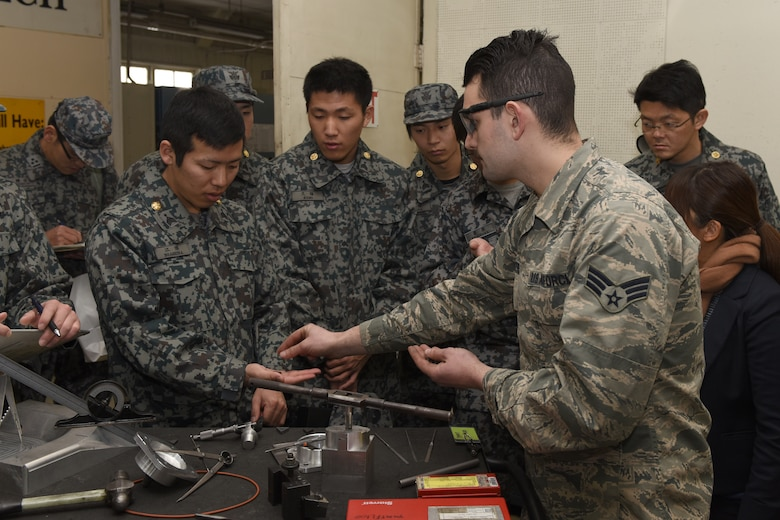 U.S. Air Force Senior Airman David Petrich, 374th Maintenance Squadron aircraft metals technology journeyman, showcases the tungsten carbide used in metals technology to Koku Jietai Cadets at a Basic Maintenance Officer Tour at Yokota Air Base, Japan, Feb. 1, 2018.