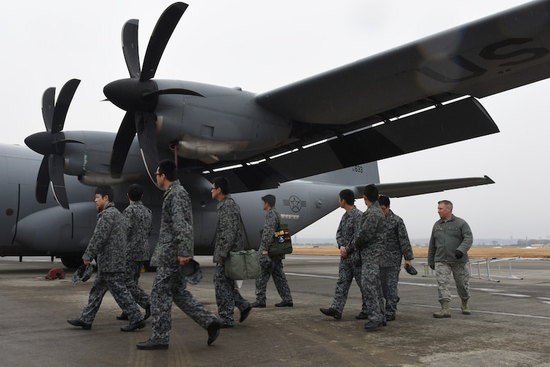 U.S. Air Force Capt. James Guthrie, maintenance exchange officer assigned to the Japanese Air Self-Defense Force's First Technical School at Hamamatsu Air Base, escorts Koku Jietai Cadets around a C-130J Super Hercules during a Basic Maintenance Officer Tour at Yokota Air Base, Japan, Feb. 1, 2018.