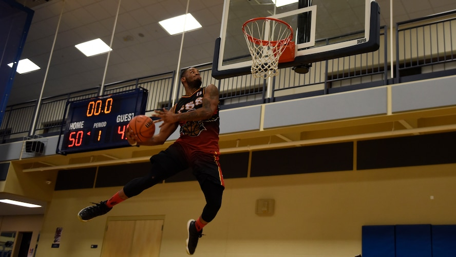 Senior Airman Andre Davis, 92nd Force Support Squadron Intramural Basketball team captain, celebrates his team's victory with dunks following the basketball season championship at Fairchild Air Force Base, Washington, Feb. 7, 2018. The 92nd FSS and the 336th Training Group basketball teams competed for the championship.  (U.S. Air Force photo/Airman 1st Class Jesenia Landaverde)