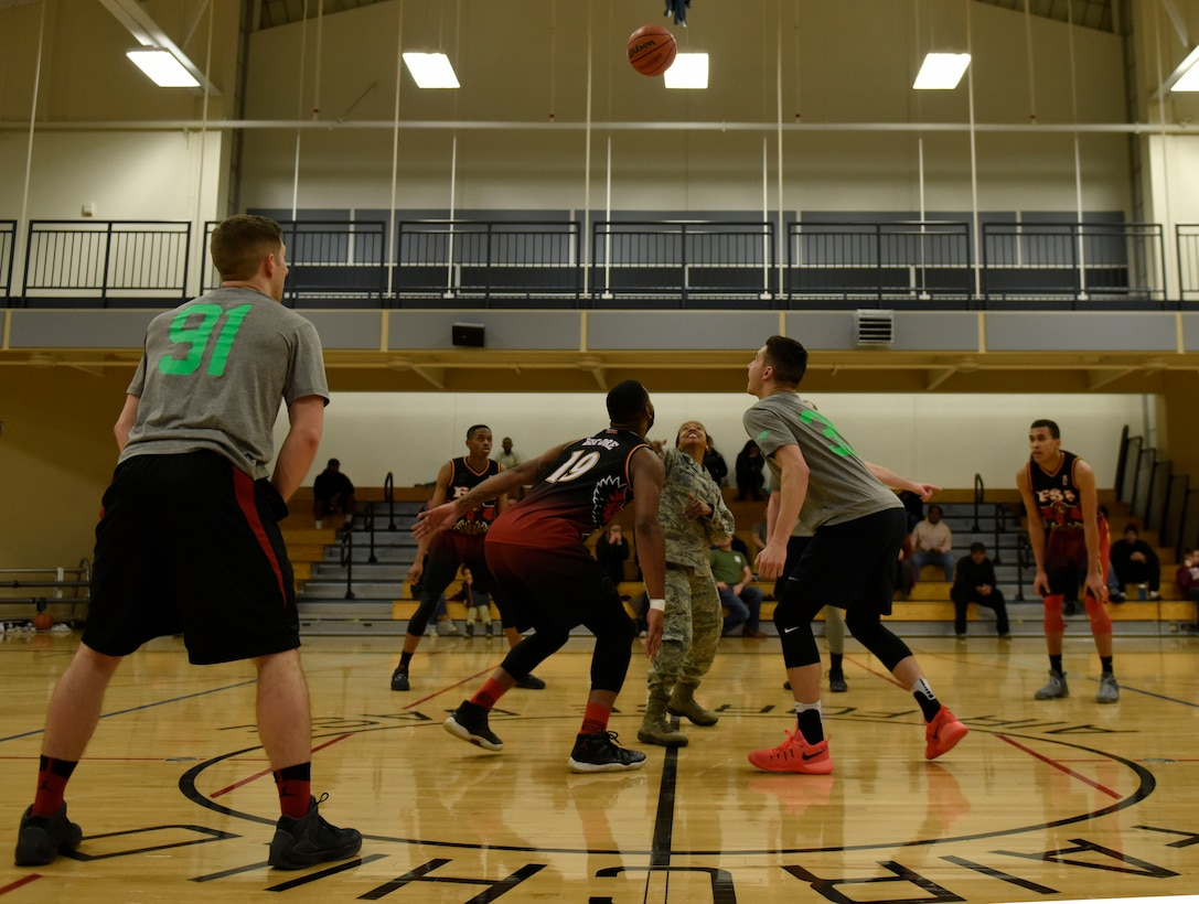 """Col. Yvonne Spencer, 92nd Mission Support Group commander, conducts a """"jump ball"""" to kick off the Intramural Basketball Season Championship at Fairchild Air Force Base, Washington, Feb. 7, 2018. The 92nd Force Support Squadron and the 336th Training Group basketball teams competed for the championship. (U.S. Air Force photo/Airman 1st Class Jesenia Landaverde)"""