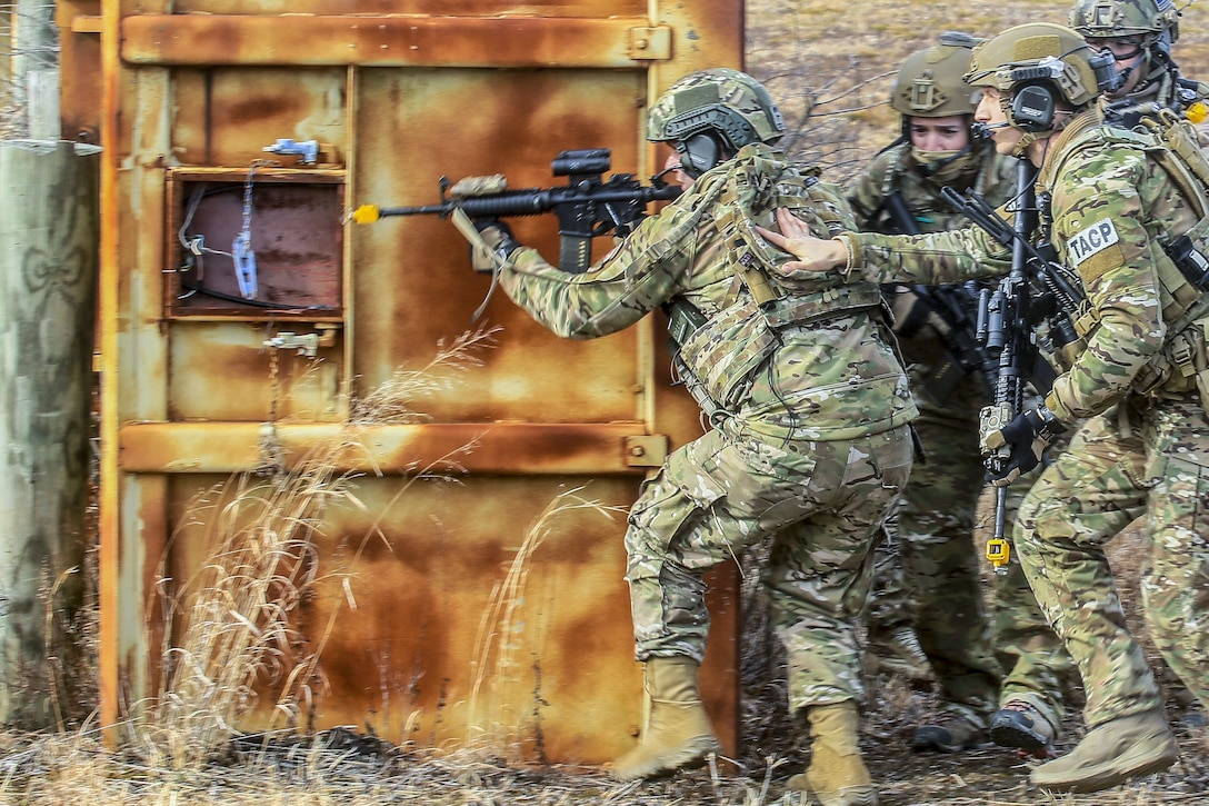 Four airmen move tactically to a target building.