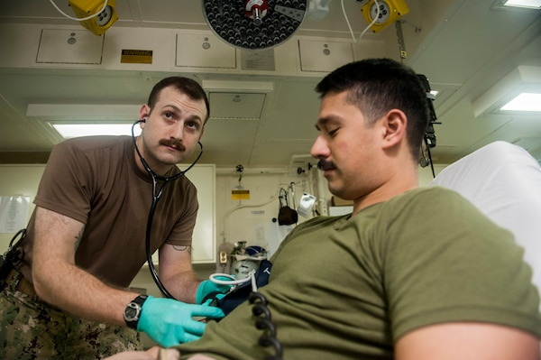 Navy Lt. Logan Moore takes a blood pressure reading from a Marine in Manama, Bahrain, Nov. 21, 2017. Moore joined the U.S. Navy Nurse Corps four years ago with the sole purpose of making a difference in others' lives. As a trauma and en route care nurse assigned to Expeditionary Resuscitative Surgical System 18, he provides critical care to patients during crisis response missions. Navy photo by Lt. Cmdr. Sandra Arnold