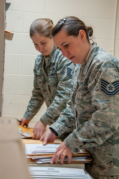 Master Sgt. Misti Rodriguez (left), Academic Coding Branch superintendent, and Tech. Sgt. Jennifer Warehime, Academic Coding Branch noncommissioned officer-in-charge, receive academic transcripts twice a week. During graduation season, they say the mail comes in large containers. Together the two update an average of between 15,000-20,000 transcripts a year in support of 130,000 total force Air Force officers including active duty, guard and reserves.  (U.S. Air Force photo/John Harrington)(U.S. Air Force photo/John Harrington)