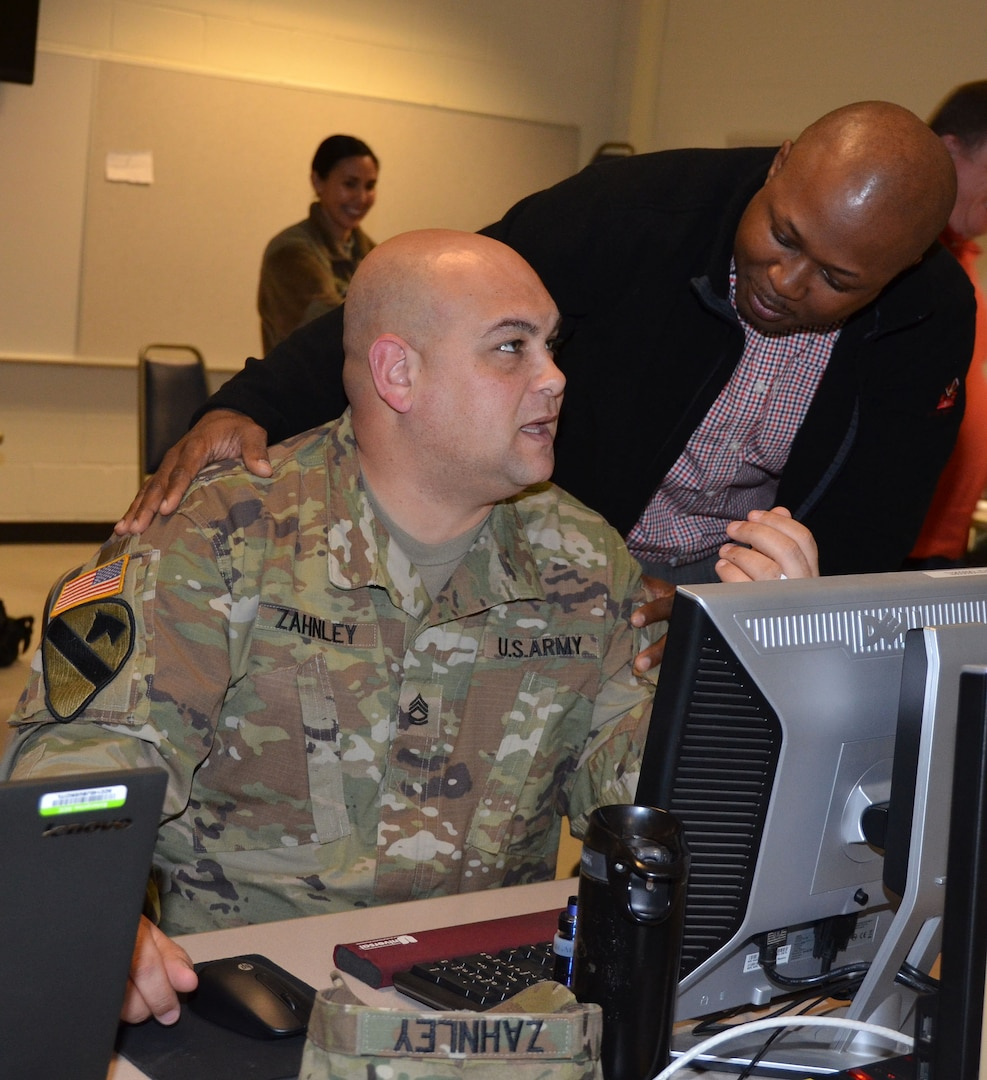 Role playing as a local vendor, Chief Warrant Officer 3 Kortney Johnson (right) seeks favor in a contract award from Sgt. 1st Class Jason Zahnley (left) during a humanitarian assistance disaster relief exercise Feb. 8 at Joint Base San Antonio-Camp Bullis. Zahnley is the NCO in charge of the 677th Contracting Team and Johnson is the property book officer for the 410th Contracting Support Brigade at JBSA-Fort Sam Houston.