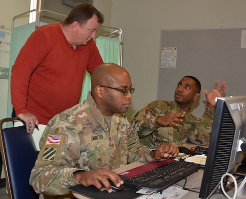 Maj. Gregory Wooten (center) provides contracting support as Mark Chase (left) and Staff Sgt. Michael Floore (right) discuss contract procedures during a humanitarian assistance disaster relief exercise Feb. 8 at Joint Base San Antonio-Camp Bullis. All are assigned to the 410th Contracting Support Brigade at JBSA-Fort Sam Houston.